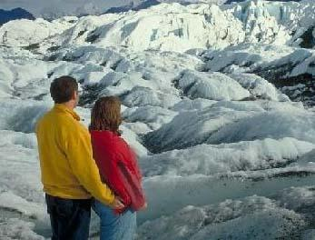 couple standing in front of Alaska glacier