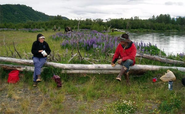two people sitting on a log in Alaska