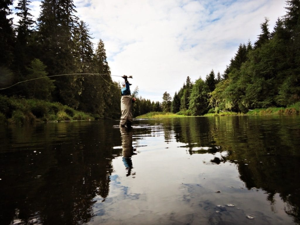 man fly fishing in Alaska river