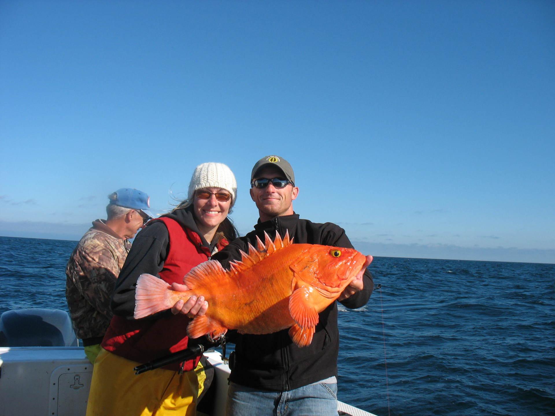 couple holding large orange fish