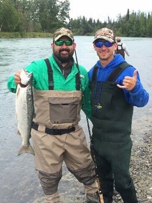 two men standing next to river holding salmon