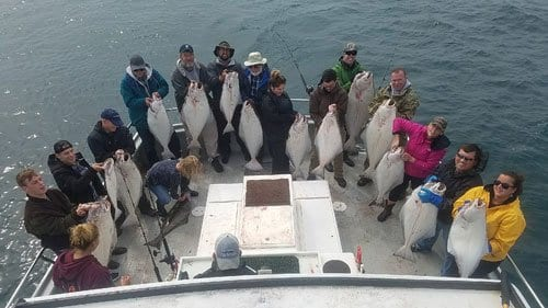 boat full of people holding halibut