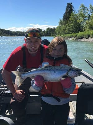 father and daughter holding a fresh caught salmon