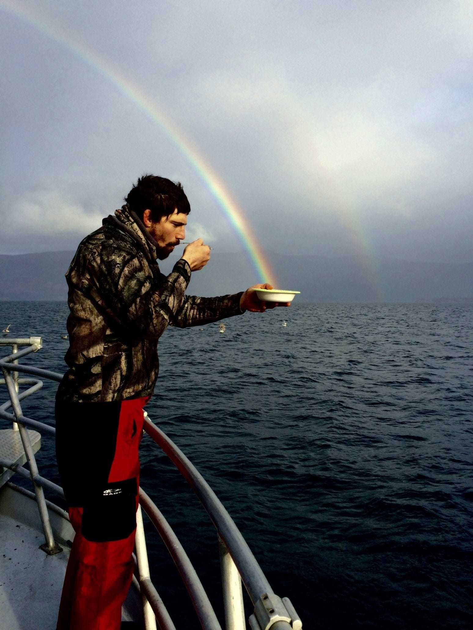 man eating cereal with rainbows in background