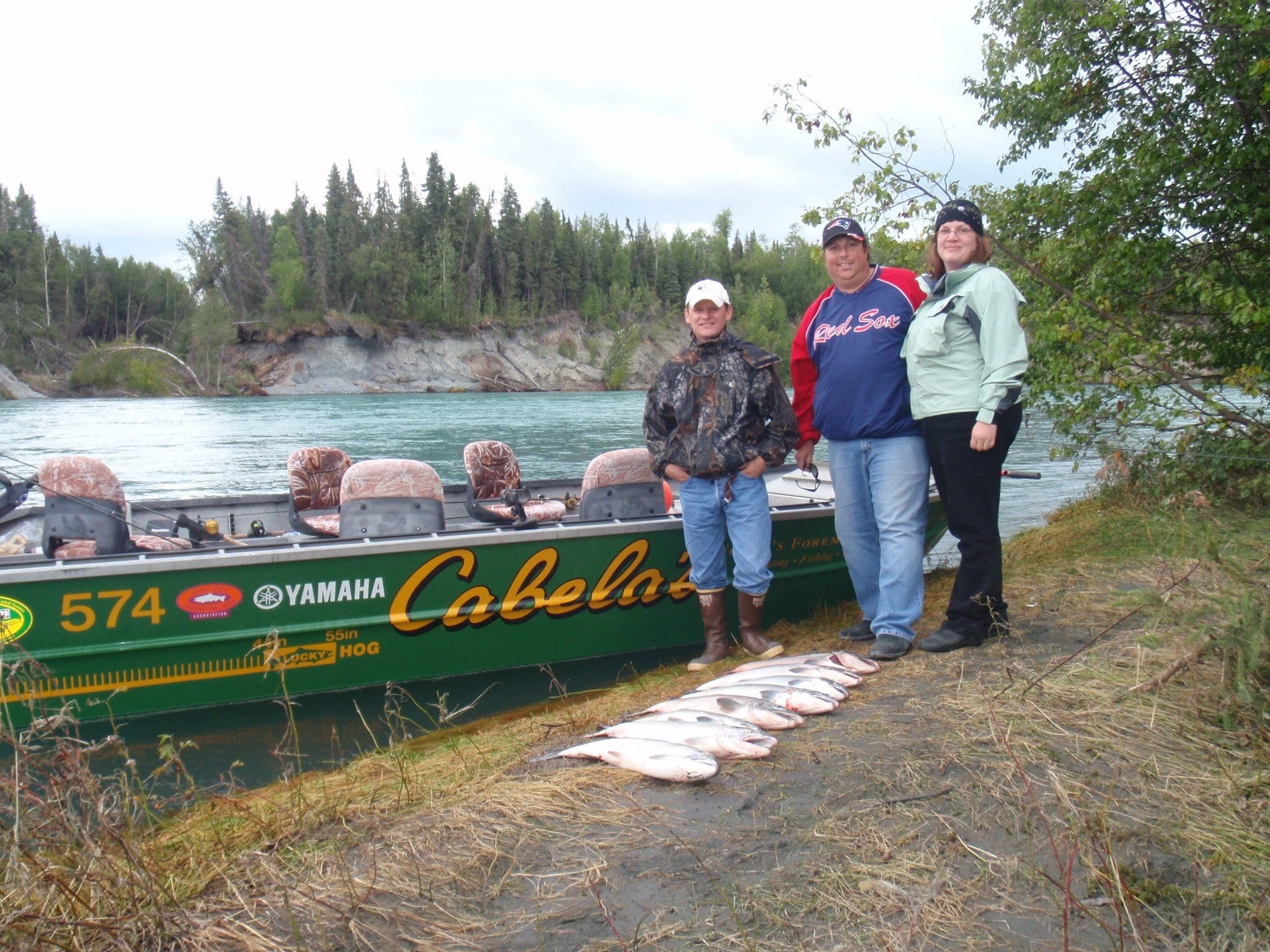3 fishers standing in front of their catch