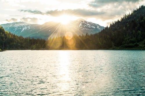 sun shining over mountain onto lake