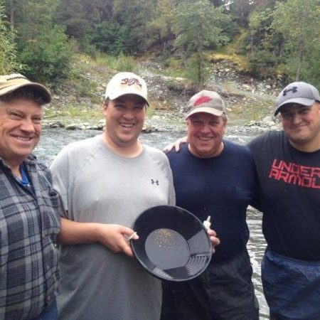 4 guys holding pan with gold