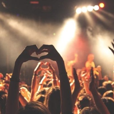 hands up in heart shape at crowded concert