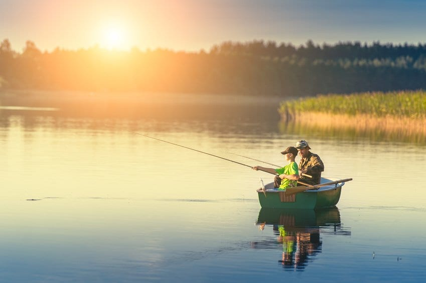 father and son fishing on a boat